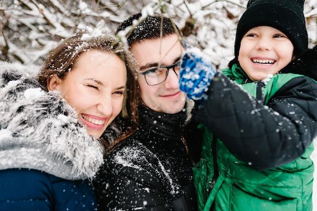 Portrait de famille heureuse marchant, jouant dans un parc d'hiver de neige, concept de vacances.