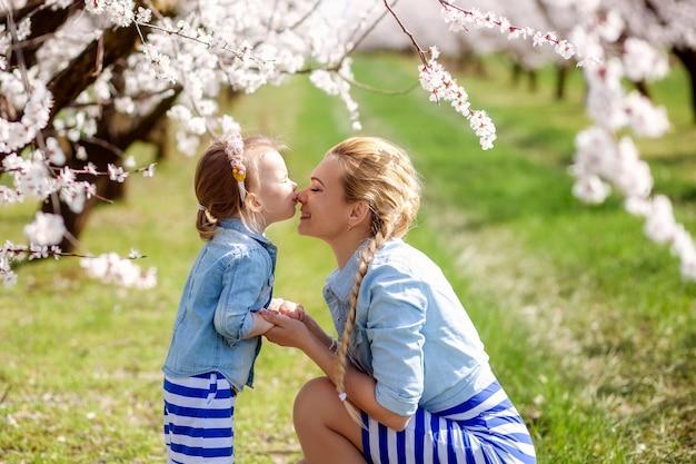 Portrait d'une famille heureuse, mère et fille sur la nature du printemps, jardins fleuris