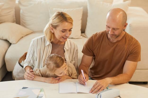 Portrait de famille heureuse mère et père aidant la petite fille mignonne s'appuyant sur l'étude à la maison