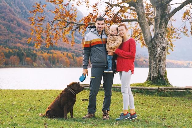 Portrait de famille heureuse mère père enfant et chien à l'extérieur l'automne sur le lac de bohinj europe