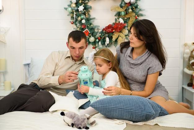 Portrait de famille heureuse à noël, mère, père et enfant assis sur le lit et allumant une bougie à la maison, décoration de noël autour d'eux