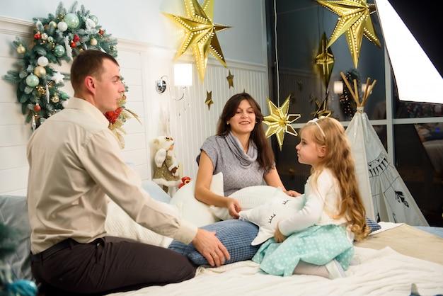 Portrait de famille heureuse à noël, mère, père et enfant assis sur le lit à la maison, décoration de noël autour d'eux.