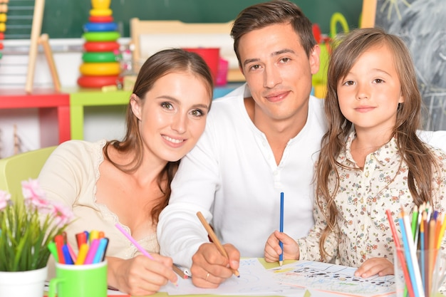Portrait d'une famille heureuse peignant à la maison