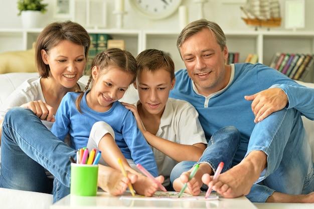 Portrait de famille heureuse peignant par leurs pieds à la maison