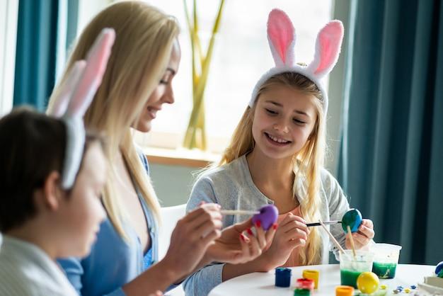 Portrait de famille heureuse peignent des œufs pendant la préparation de pâques. ils sont assis à table. concentrez-vous sur la fille.