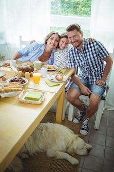 Portrait de famille heureuse prenant son petit déjeuner ensemble