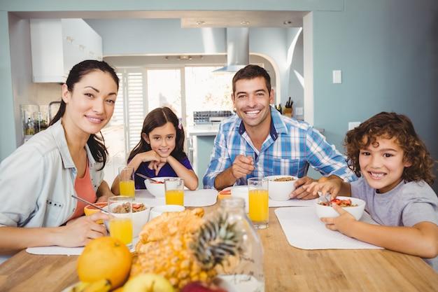 Portrait de famille heureuse prenant son petit déjeuner