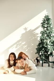 Un portrait de famille heureuse près de l'arbre de noël avec une boîte à la maison