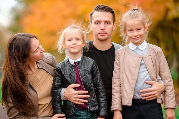Portrait de famille heureuse de quatre personnes au jour de l'automne