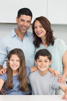 Portrait d'une famille heureuse de quatre personnes dans la cuisine
