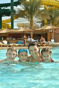Portrait d'une famille heureuse s'amusant dans la piscine