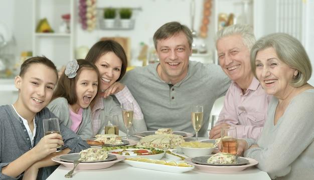 Portrait de famille heureuse à la table avec une cuisine savoureuse