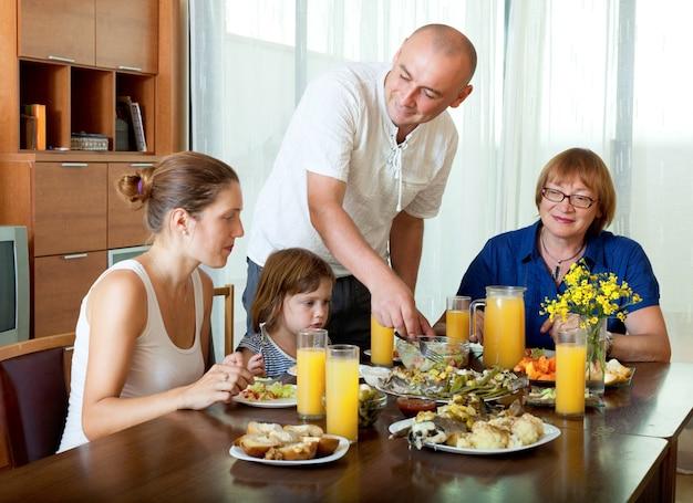 Portrait de famille heureuse trois générations posant ensemble sur une table saine