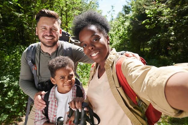 Portrait de famille heureuse de trois personnes faisant portrait de selfie sur le téléphone mobile pendant leur randonnée