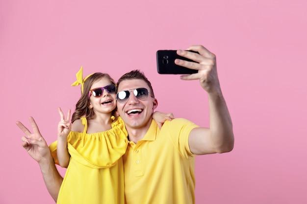 Portrait de famille heureuse en vêtements jaunes avec des lunettes de soleil