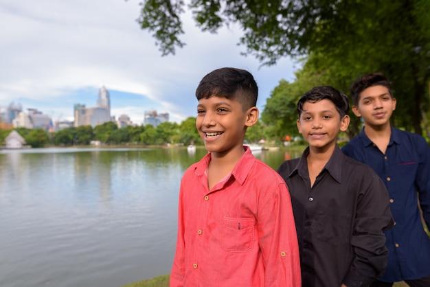 Portrait de famille indienne se détendre ensemble dans le parc