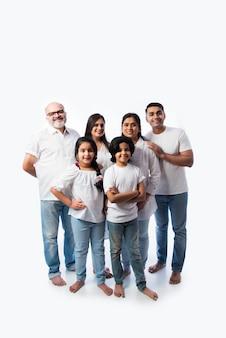 Portrait de famille indn avec grands-parents, parents et enfants contre un mur blanc en draps blancs