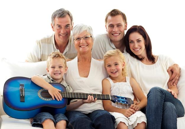 Portrait de famille jouant de la guitare à la maison