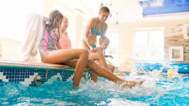 Portrait d'une famille joyeuse et heureuse assise au bord de la piscine et éclaboussant de l'eau avec les pieds. famille jouant et s'amusant à la piscine