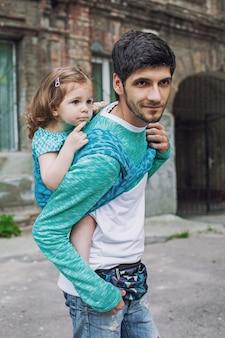 Portrait de famille moderne avec père et fille en bas âge dans un porte-bébé