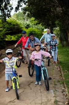 Portrait de famille multi-génération debout avec vélo dans le parc