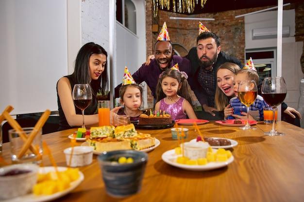 Portrait de famille multiethnique heureuse célébrant un anniversaire à la maison