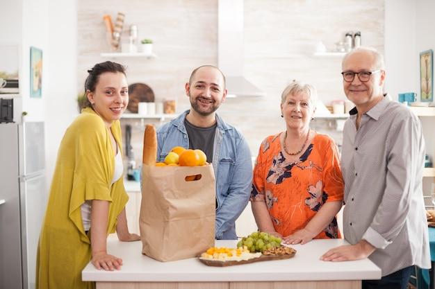 Portrait de famille multigénération souriante à la caméra dans la cuisine avec paparbag d'épicerie et une variété de fromages