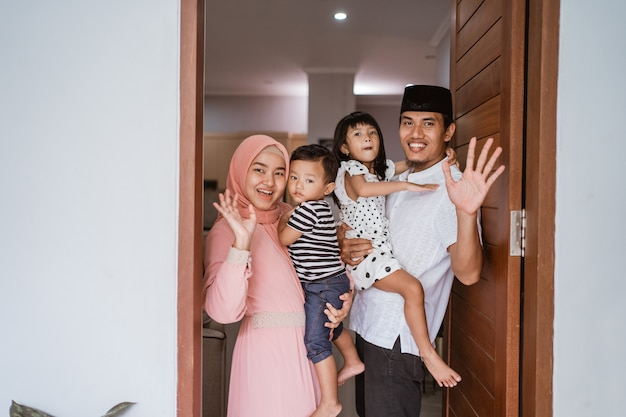 Portrait de famille musulmane debout devant leur porte d'entrée accueil invité d'accueil à la maison lors de la célébration de l'aïd mubarak