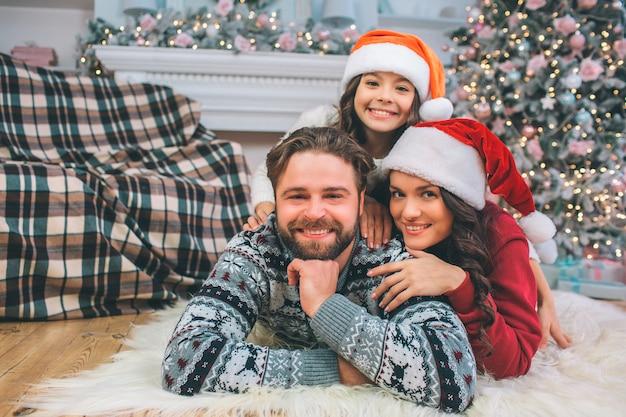 Portrait de famille de personnes gisant sur le sol et pose. ils sourient. l'enfant est au-dessus de ses parents. la femme yong se penche vers l'homme. ils ont l'air festif. femme et fille porte des chapeaux rouges.