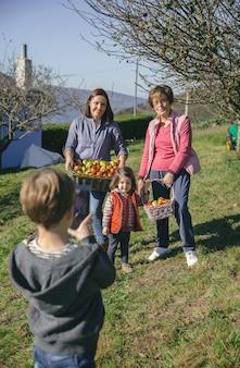 Portrait de famille avec des pommes biologiques fraîches dans un panier en osier posant pendant qu'un garçon mignon prend une photo avec une tablette électronique. concept de temps libre en famille.