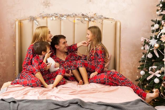 Portrait de famille en pyjama allongé sur le lit. mère, père et deux enfants s'amusant dans la chambre. concept de noël et nouvel an
