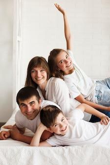 Portrait de famille souriante allongée sur un lit à la maison