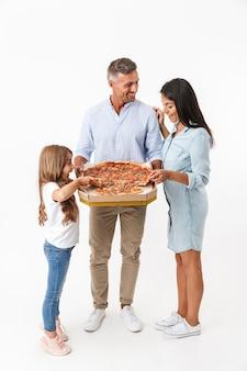 Portrait d'une famille souriante, manger de la pizza