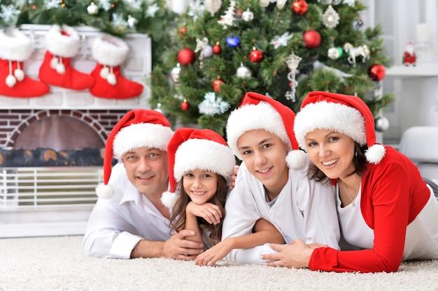 Portrait de famille souriante posant près de sapin de noël