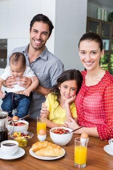 Portrait de famille souriante à la table du petit déjeuner