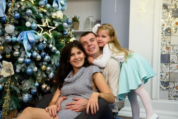 Portrait de famille sympathique regardant la caméra le soir de noël.