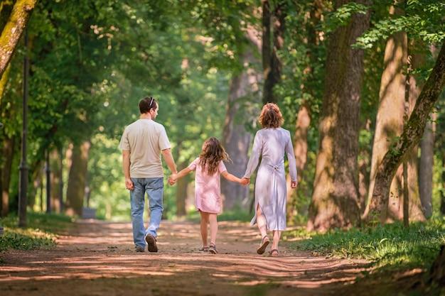 Portrait d'une famille traditionnelle heureuse lors d'une promenade dans un parc d'été, vue de dos sans visage