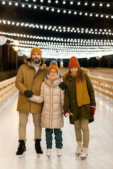 Portrait de famille de trois personnes souriant à la caméra en patinant sur la patinoire du parc