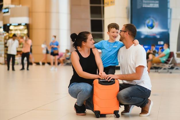 Portrait de famille voyageant avec des valises à l'aéroport