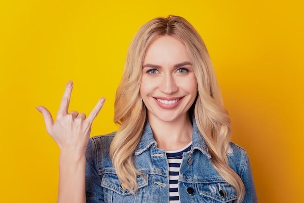 Portrait d'une fan girl hipster grossier montrant des cornes rock and roll geste sur fond jaune