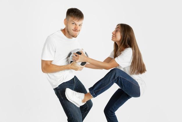 Portrait de fans de football ou de football de beau jeune couple sur fond de studio blanc. expression faciale, émotions humaines, publicité, concept sportif. femme et homme sautant, criant, s'amusant.