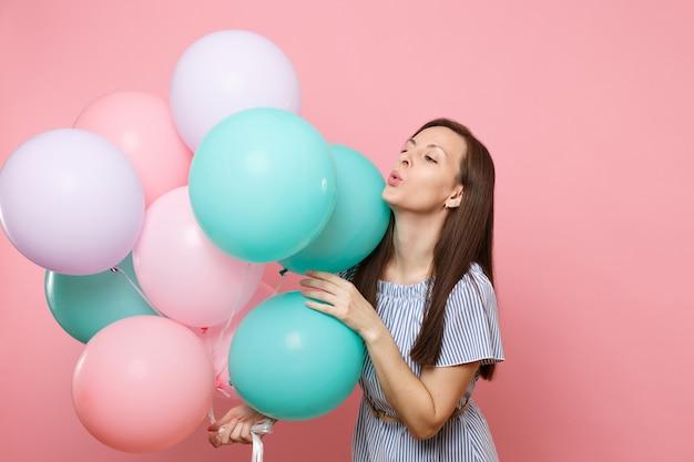 Portrait de fascinante jeune femme tendre vêtue d'une robe bleue tenant des ballons à air colorés isolés sur un fond rose tendance brillant. fête d'anniversaire, concept d'émotions sincères.