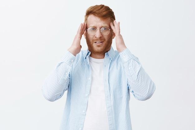 Portrait de fatigué entrepreneur masculin beau avec des cheveux roux et une barbe dans des verres, tenant les mains sur les tempes et regardant flou, ayant mal à la tête