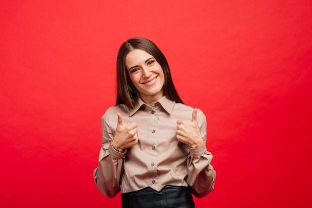 Le portrait féminin isolé sur fond de studio rouge.