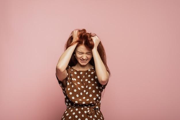 Le portrait féminin isolé sur mur rose. colère. la jeune femme émue, en colère et effrayée. qu'est-ce que c'est