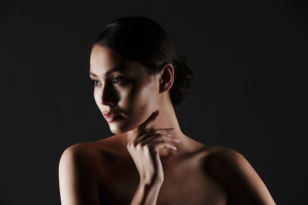 Portrait, de, féminin, jeune femme, à, cheveux foncés, dans, chignon, regarder côté, dans, basses lumières, isolé, sur, noir