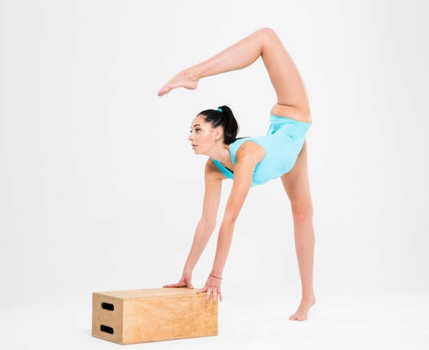 Portrait de femme acrobate en costume de gymnaste qui s'étend isolé sur un mur blanc