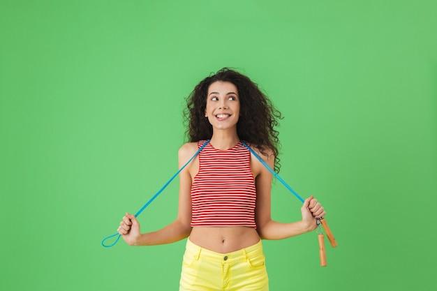 Portrait d'une femme active de 20 ans portant des vêtements d'été s'entrainant et faisant des exercices avec une corde à sauter en se tenant debout sur le vert