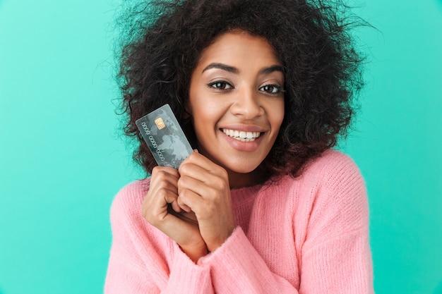Portrait de femme adorable aux cheveux hirsutes tenant une carte de crédit en plastique et souriant sincèrement, isolé sur mur bleu