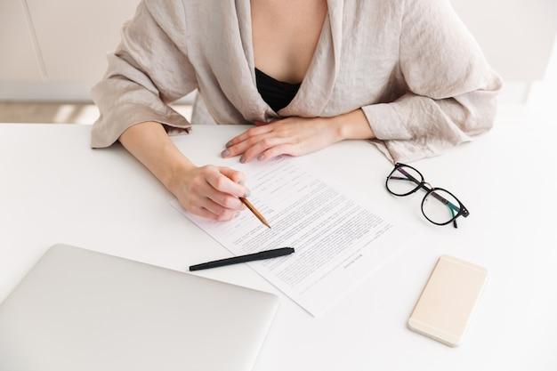 Portrait de femme adulte caucasienne portant une robe travaillant avec des documents, assis à table dans le lieu de travail à domicile